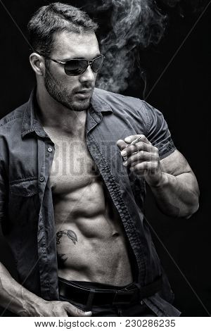 Macho Male Smoking Cigar In Front Of Black Background