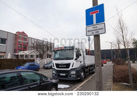Nuernberg / Germany - March 4, 2018: Man Flatbed Truck Stands On Roadside Near A German Traffic Sign