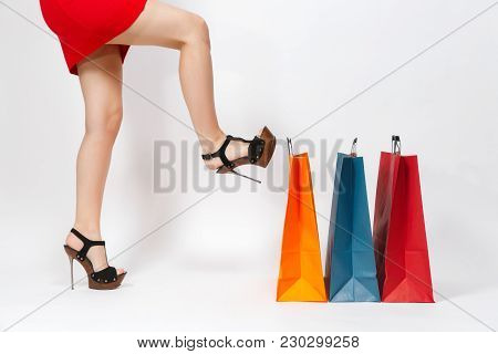 Slender Long Female Legs In Black Sandals, Caucasian Woman In Red Dress Kicking Multi Colored Packet
