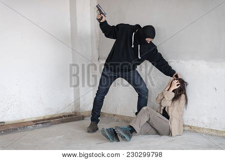 Black Masked Robber In Black Long Sleeve Shirt Is Holding A Gun And Intimidate A Woman , He Is Pulli