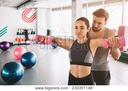Two People Are Standing In The Finess Room. The Guy Is Helping His Girfriend To Do Push Ups With Dum