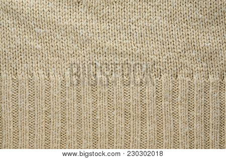 Beige Texture of a Knitted Sweater with Two Types of Knitting. Knit texture as background.