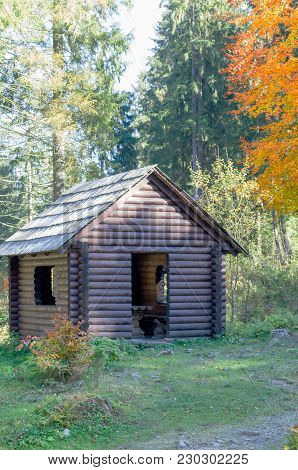 Shed In A Woods. Wooden House In The Forest. The House Is Made Of Log House. Wooden House In The For
