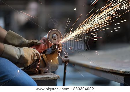 Selective Focus At Steel Cutter. Man Use Electric Steel Cutter And Clamp Metal In Factory And Throwi