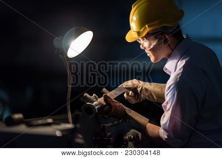 Mechanic Engineer Turner Miller Verifies The Accuracy Of Manufacturing Steel Parts With A Scale The