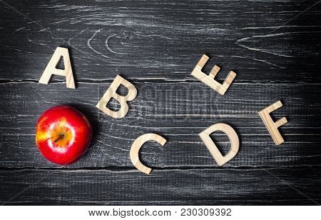 Red Apple And Alphabet Made Of Wooden Letters On A Dark Background Of A School Board. Apple For The