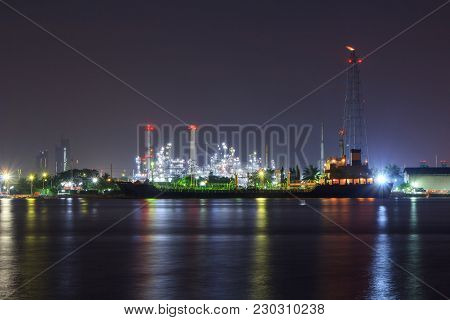 Oil Refinery At The River In Night Time / Big Factory In Night Time