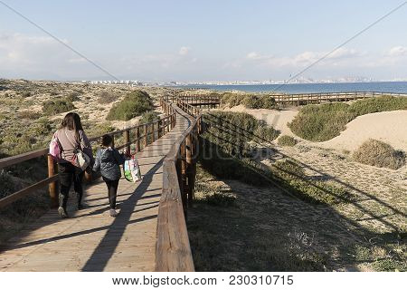 People Walking Through The Wooden Walkway In The Arenales Del Sol.
