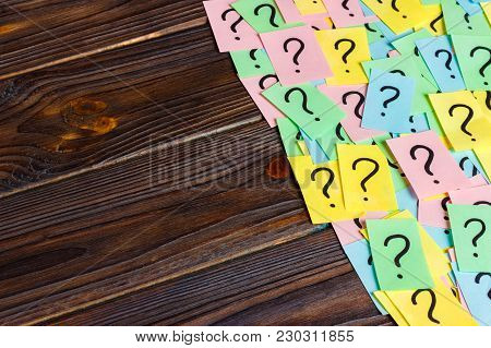 Just A Lot Of Question Marks On Colored Papers On Wood Background.