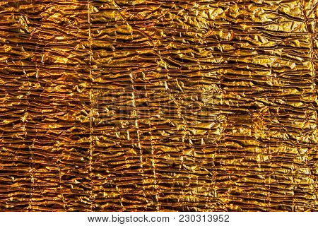 Abstract Background Image Structure Texture Golden Shiny Foil With Dents And Wrinkles.