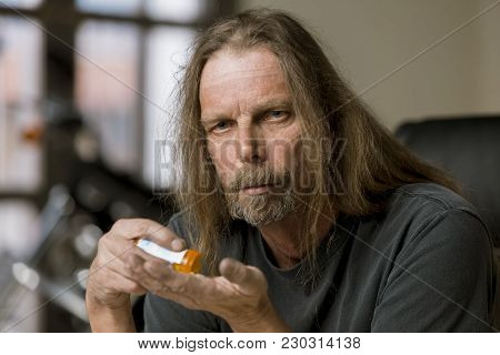 Man Holding An Opioid Pill And Bottle