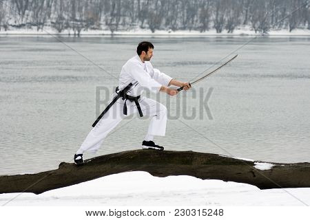 The Ninja In White Kimono With Sword Is Practicing Martial Arts On Wood On Riverside At Winter.