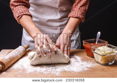 Kneading The Dough,  A Woman Is Kneading Pizza Dough On A Table.