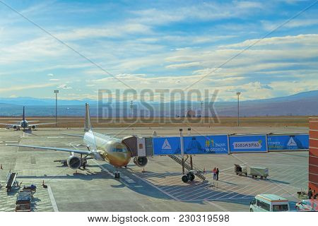 Tbilisi, Georgia, 2017-12-07: Airplane Of Gulf Avia In Tbilisi Airport With Jetway ramp Waiting For
