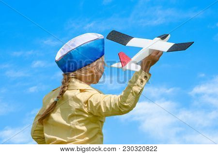 Happy Baby Girl Kid Playing With Toy Airplane Against Blue Summer Sky Background. Concept - Inoculat