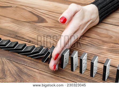 Woman's Hand Stopping Domino Effect On The Desk. Close Up.