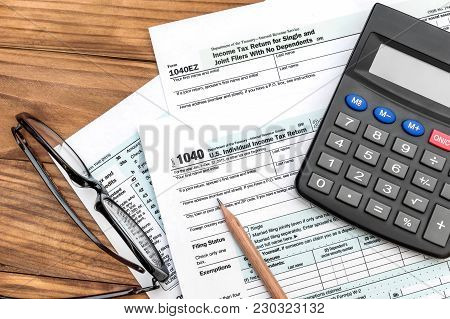 Tax Forms With Calculator, Pencil And Eyeglasses On The Table. Top View. Business And Tax Concept.