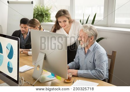 Smiling Young Manager Helping Senior Worker With Funny Computer Work In Office, Mentor Teacher Train