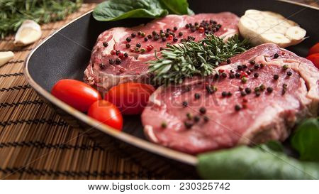 Fresh And Raw Beef Steaks With Rosemary And Pepper
