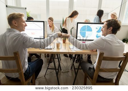 Smiling Male Coworkers Fist Bumping At Workplace Working On Computers In Coworking Office, Motivated