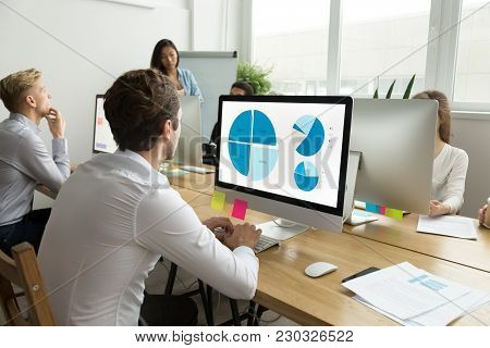 Employee Analyzing Statistics Data Charts On Computer Screen Working In Office With Multiracial Team
