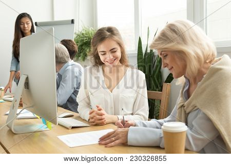Older Businesswoman Signing Paper Contract With Smiling Female Manager In Coworking Office, Senior C