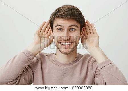 Ready To Listen Latest Gossips. Portrait Of Handsome Excited European Man Holding Palms Near Ears An
