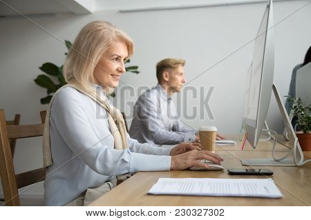 Smiling Aged Businesswoman Office Worker Working On Pc Desktop Computer At Modern Workplace, Happy A