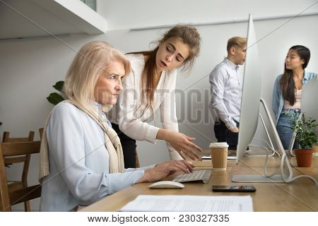 Young Team Leader Correcting Offended Senior Employee Working On Computer In Office, Female Manager