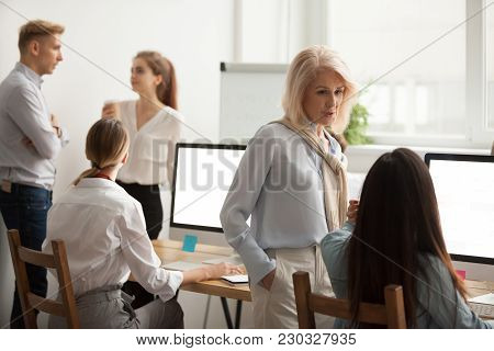 Serious Senior Woman Talking To Young Employee Discussing New Idea In Office, Corporate Team Staff W