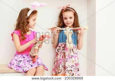 Portrait Of Little Girls In Easter Pink Bunny Ears Holding Toy Bunnies. Little Sisters In Easter Bun