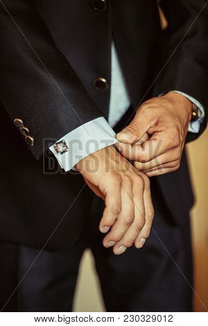 Unknown Manfastens The Cuffs Of His Shirt. Morning Of The Groom.the Groom Fastens The Cuff Links To