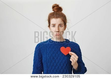 Nobody Loves Me. Portrait Of Upset Cute Redhead European Woman With Bun Holding Paper Heart Near Che