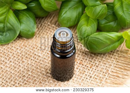 A Bottle Of Basil Essential Oil With Fresh Basil Twigs In The Background