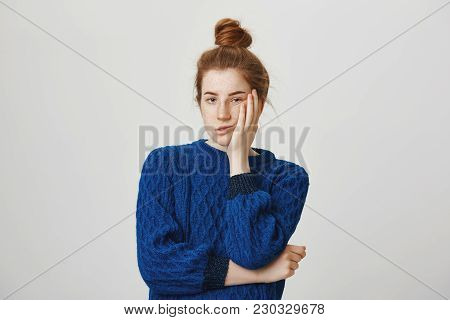 Cute Redhead Annoyed Woman Standing In Winter Sweater, Holding Palm On Cheek And Leaning Face On It,