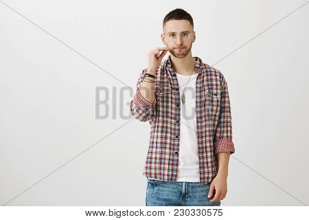 Bothered Attractive Guy With Beard, Wearing Trendy Glasses And Plaid Shirt, Stretching Gloomy Smile