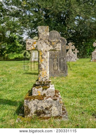 Old Plain Stone Cross With Moss And Lichen , Standing On Grass In A Graveyard.
