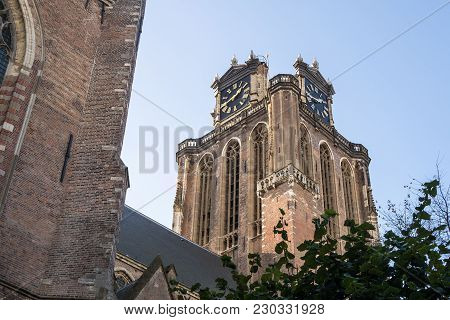Church Tower Of The Grote Kerk In Dordrecht, Netherlands, Seen From Below, Above A Tree.