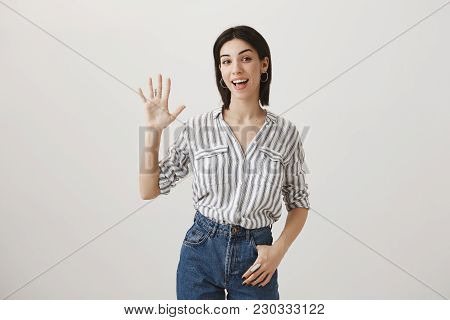 Friendly Woman Met Her Girlfriends And Ready To Go Shopping. Studio Shot Of Attractive Girl Raising