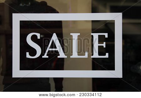 Sale Sign On The Shop Window. Retail Image Of A White Sale Sign In A Clothing Store Window