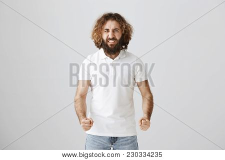 Anger Boils His Blood. Portrait Of Angry Eastern Guy With Beard And Curly Hair Clenching Fists And M