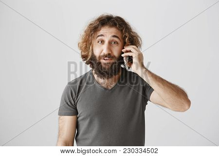 You Do Not Say. Portrait Of Charming Curly-haired Eastern Man With Beard Talking On Smartphone With
