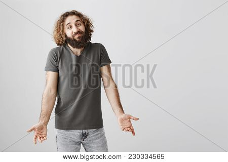 You Cannot Escape Fate. Shot Of Clueless Shrugging Handsome Eastern Guy With Beard Holding Palms Dow