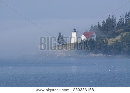 Foggy Island Lighthouse In Maine Is Iluminated By The Sun Breaking Through The Fog
