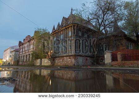 Old Wooden Mansion In Gothic Style In Astrakhan Reflecting In The Pool.