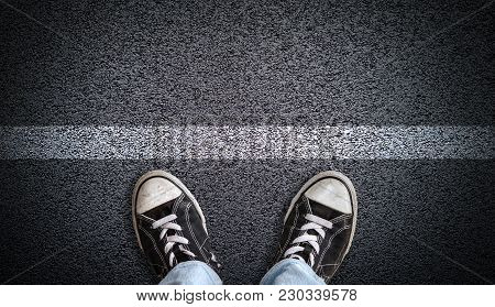 A Teenager In Jeans And Canvas Shoes Standing On Asphalt Road Behind A Line With Copy Space. Concept
