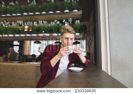 A Positive Young Man Drinks Coffee In A Cozy Cafe And Looks At The Camera. Lunch In A Cozy Cafe.