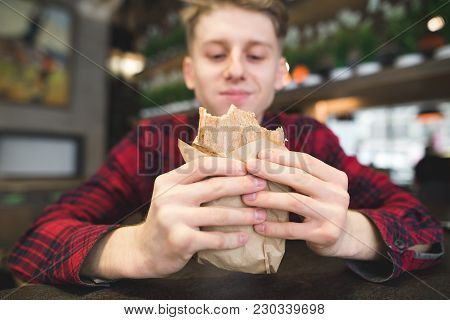 A Student Eats A Sandwich In A Cozy Cafe. A Young Man With A Happy Look Looks At The Panini Sandwich