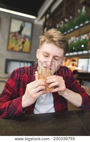 A Young Man Sits In A Cafe And Holds Up A Panini Sandwich. A Student Dishes A Sandwich In A Cafe. A