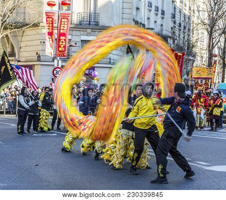 Paris, France-february 25,2018: Dynamic Image Of A Team Of Men Performing With The  Chinese Dragon D